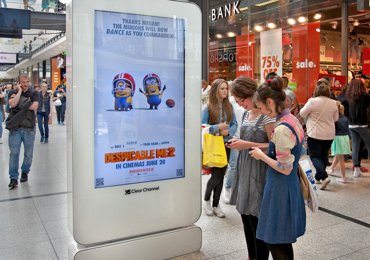 Two girls standing in front of a digital billboard of the movie Despicable Me 2