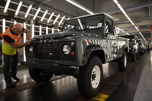 An employee inspects the bonnet of a Land Rover Defender as it moves down the inspection line at Tata Motors Jaguar Land Rover vehicle-manufacturing plant in Solihull, UK. Picture: BLOOMBERG/SIMON DAWSON