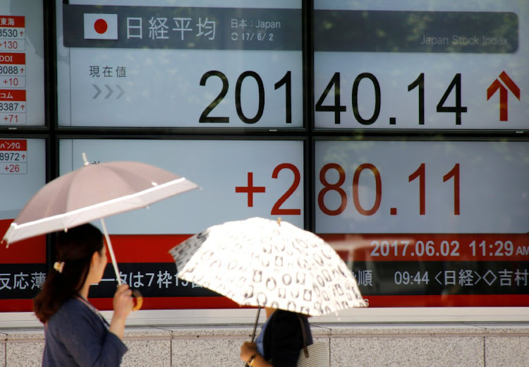 Women holding parasols, look at an electronic board showing Japan's Nikkei average outside a brokerage in Tokyo, Japan. Picture: REUTERS/TORU HANAI