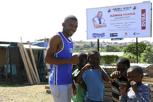 Azinga Fuzile poses near a billboard with his image in Duncan Village, East London, in the Eastern Cape.
