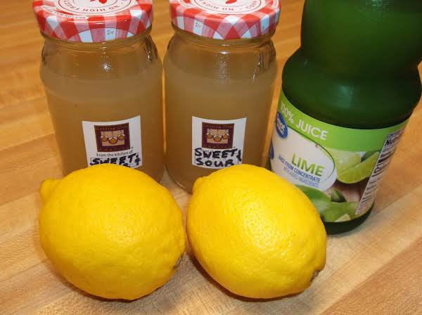 Bottled Sweet And Sour Mixer On Counter Next To Lemons And Lime Juice.