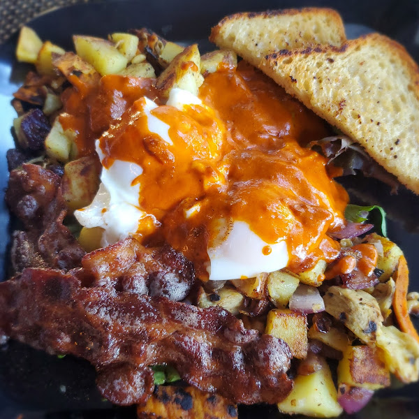 Poached eggs over veggie yam and artichoke hash smothered in red sauce with a side of bacon candied with cinnamon and cocoa