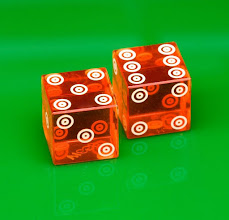 Photo: Translucent red dice on green background