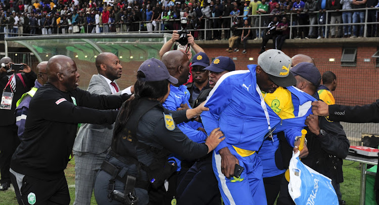 Mamelodi Sundowns coach Pitso Mosimane at the centre of scuffle broke broke out between Mosimane and the head of the security company (not in this picture) that does duty for AmaZulu FC's home matches following an Absa Premiership match at King Zwelithini Stadium in Umlazi, Durban, on Sunday September 16 2018. Sundowns' team manager Peter Ndlovu (wearing a red tie) is seen trying to pull the coach away.