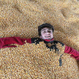 Boy Buried in Corn by Kristine Nicholas - Novices Only Portraits & People ( farm, child, food, yellow, boy, corn, hat, kid,  )