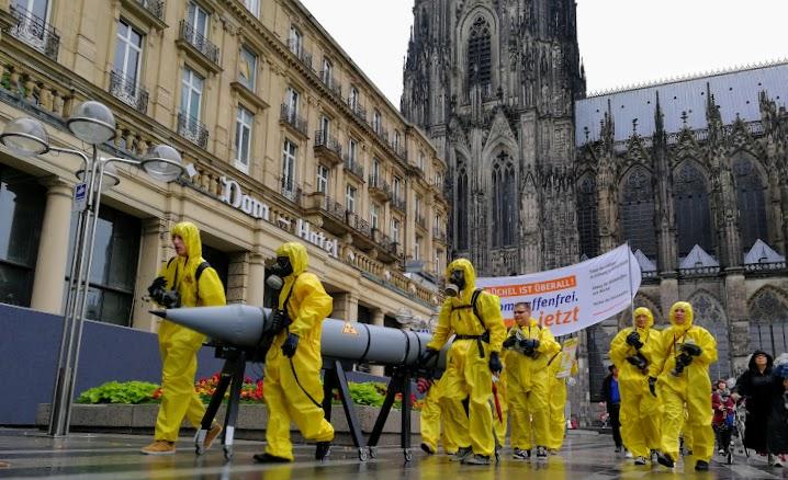 Atomwaffengegner in gelben Overalls mit der Attrappe einer Büchel-Atombombe, im Hintergrund Dom-Hotel und Dom.
