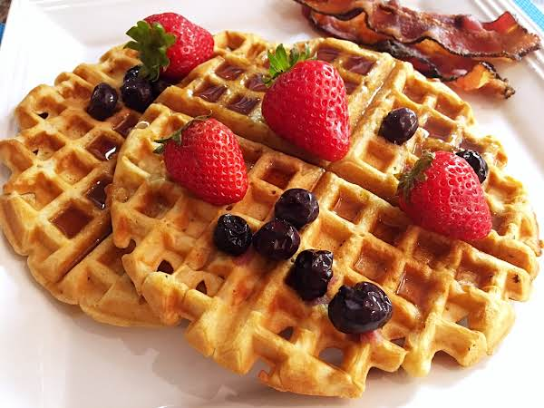 Waffles On A White Plate With Strawberries, Blueberries, Bacon And Syrup.