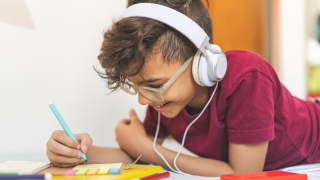 young boy with headphones on coloring