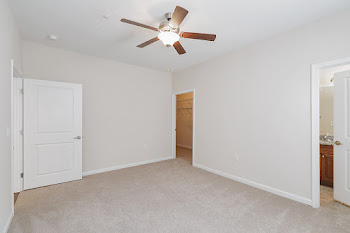 Living room with light carpet, ceiling fan, and attached bathroom