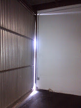Photo: West side door to hangar gap.  Need to replace wall trim with Trex, and add gap seal.