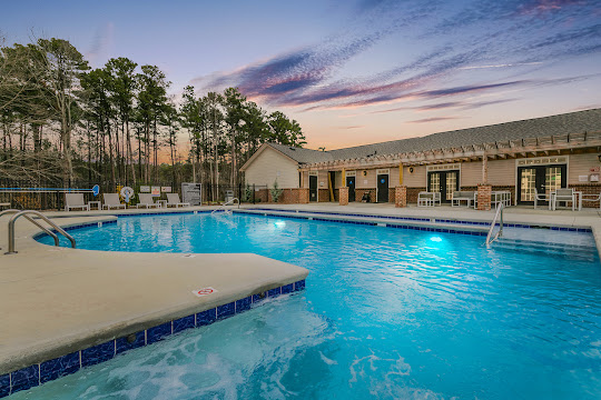 Swimming pool with view of clubhouse and apartment building at dusk