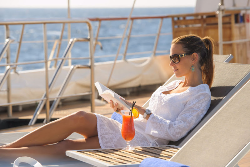 Enjoy a good book + cool drink + sunshine on deck on your Ponant cruise.