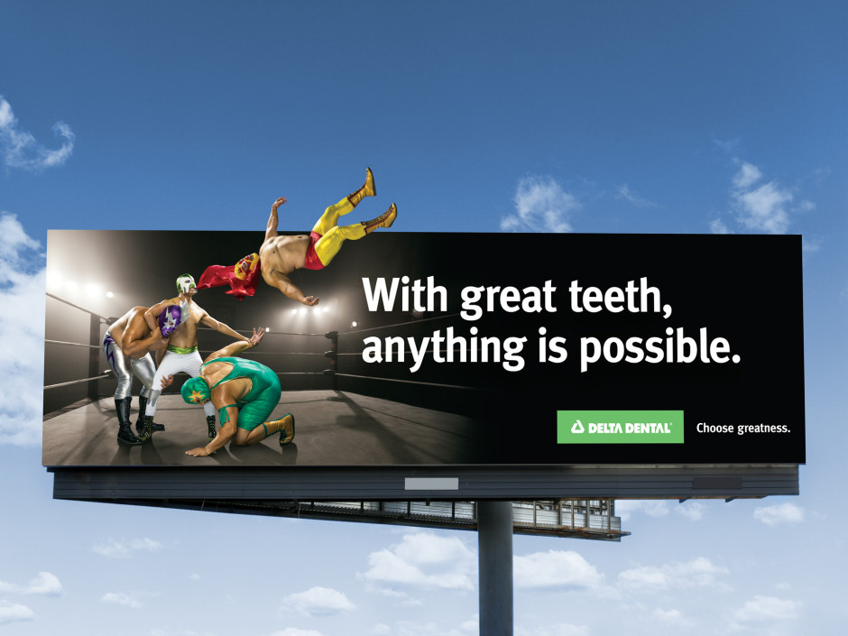 "Delta Dental's billboard stating ""With great teeth, anything is possible."", next to 4 wrestlers fighting in the ring"