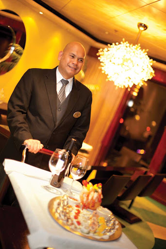 ncl_Crew_Butler.jpg - A butler with a tray of canapes and Champagne in The Haven on Norwegian Cruise Line.