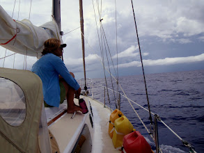 Photo: Anne watching squalls dance about during our crossing to Abaco