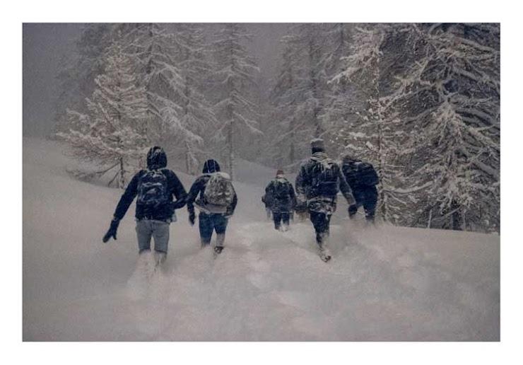 Des exilés descendent la montagne de Montgenèvre, la neige leur arrive aux genoux, ils marchent depuis deux heures déjà. Nuit du 14 mars 2019.