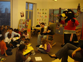 """Photo: Josh Mora from ComCast Sports Net, the author of The Magic Uniform, reads aloud to 3rd graders while """"Tommy Hawk"""" animates the story."""