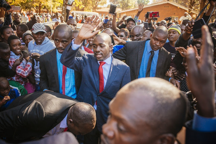MDC Alliance leader Nelson Chamisa, centre, waves to supporters as he arrives to cast his vote at a polling station in Harare, Zimbabwe, July 30 2018. Picture: BLOOMBERG/WALDO SWIEGERS