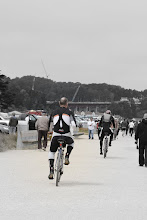 Photo: Some sailors cycle along the promenade to the storage area with their wet-suits on and center boards under their arms!