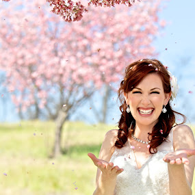 Bride Showered by Cherry Blossom Petals by Kim Wilson - Wedding Bride ( person, photograph, petals, exterior, bright, exuberance, spring, people, woman, sunny, exhilarate, happy, lifestyle, gown, smile, bride, flowers, white, image, 30s, adult, young, blossoms, cherry, bridal, female, wedding, horizontal, outdoors, trees, shower, sleeveless, outside )