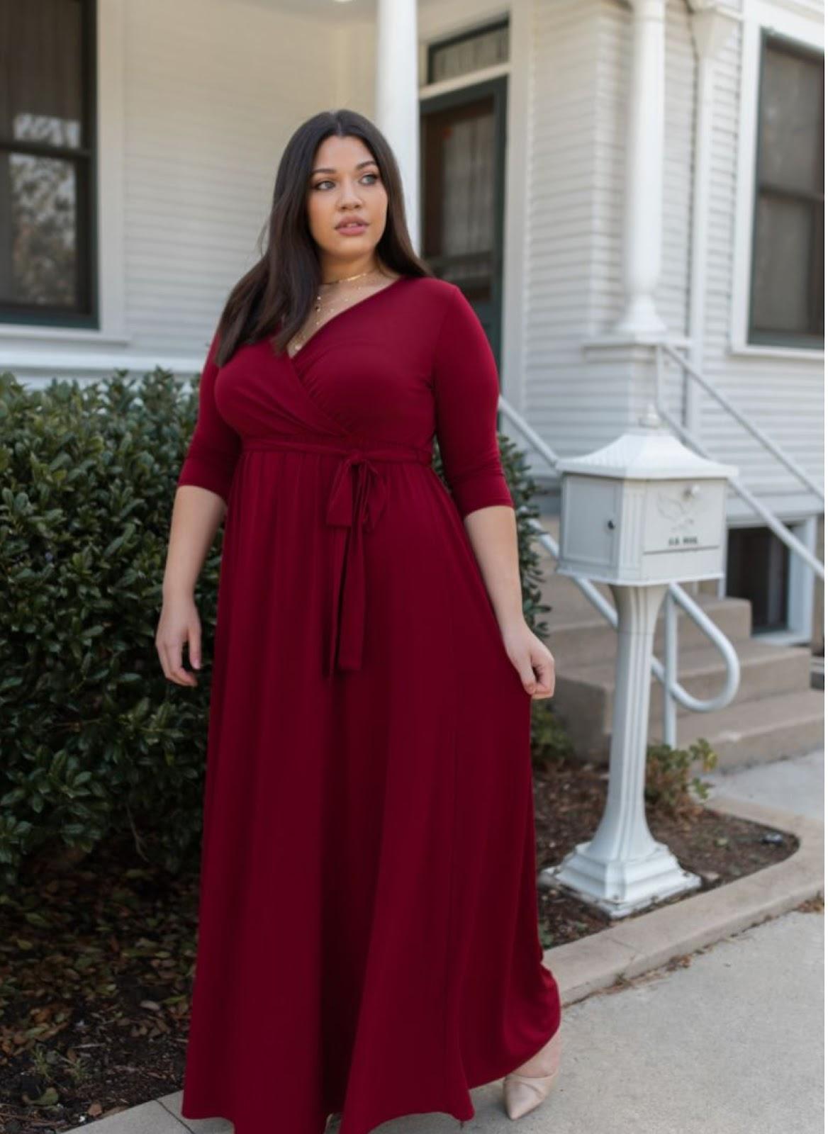 A woman is wearing a dark red wrap dress