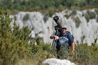 Gustav Kiburg draagt in de bergen een camera met grote telelens op een statief