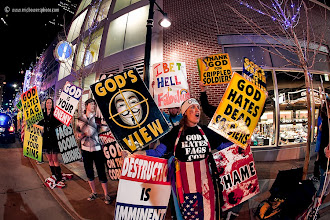 Photo: The anti-gay Westboro Baptist Church stages a protest in response to a screening of the film Red State at the Midland Theatre in Kansas City, MO. In this shot one of the counter protesters snuck in behind the woman in front to hold his own sign.