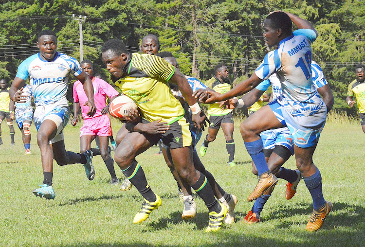 Kabras RFC Captain Bryceson Egesa runs past MMUST RFC players during a match at Kakamega show ground on Saturday