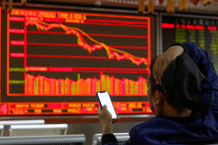 An investor sits in front of displays showing stock information at a brokerage office in Beijing, China. Picture: REUTERS/THOMAS PETER