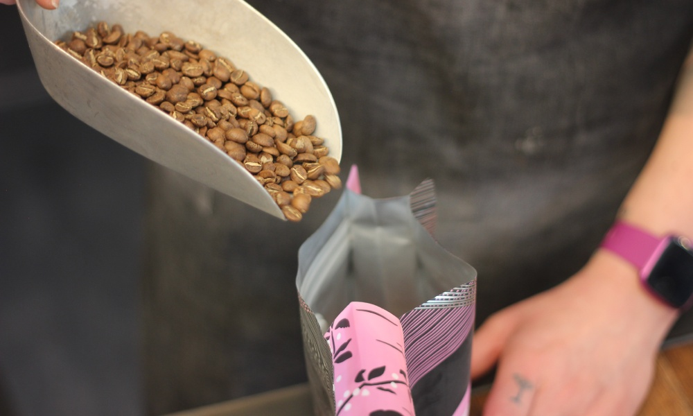 putting beans into recyclable coffee bags