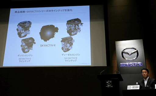 Mazda president Masamichi Kogai presents a slide show about its new engine, to be called SKYACTIV-X, in Tokyo, Japan, on August 8 2017. Picture: REUTERS