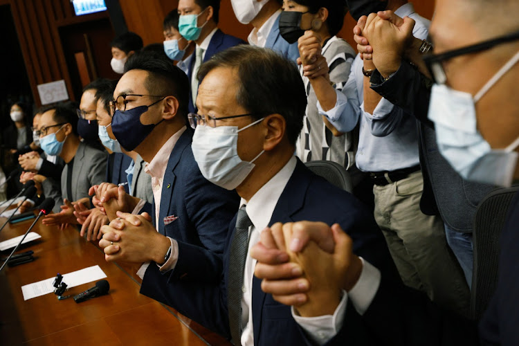Pan-democratic legislators including Kenneth Leung, Dennis Kwok, Wu Chi-wai, Alvin Yeung and Kwok Ka-ki join their hands together during a news conference as they threated mass resignations amid reports of Beijing plans to disqualify four opposition lawmakers, in Hong Kong, November 9 2020. Picture: REUTERS/TYRONE SIU