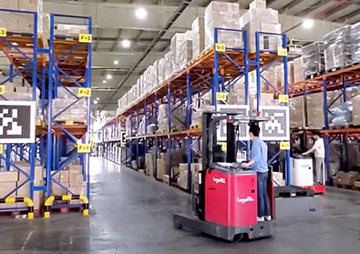 A driver and their red forklift are driving through a warehouse.