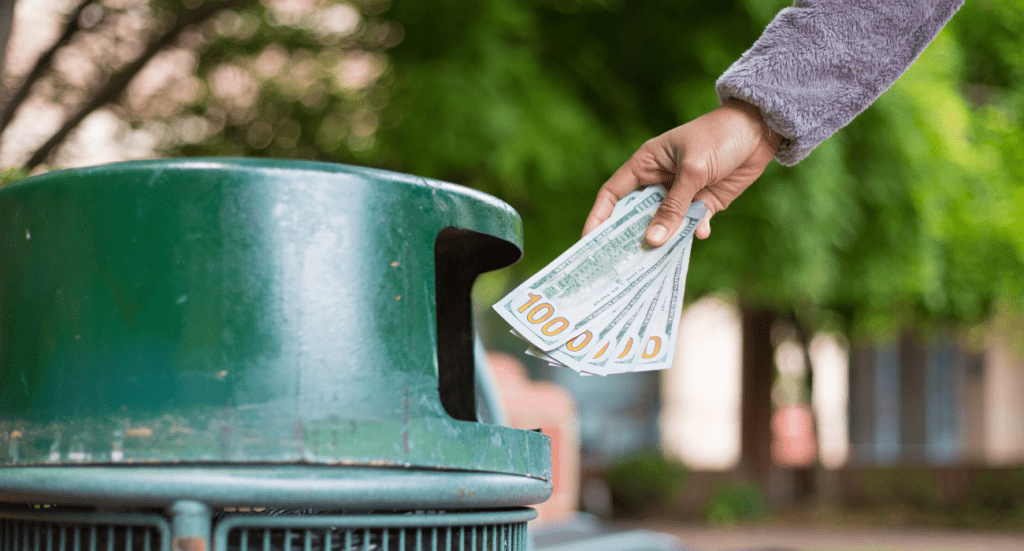 person throwing money into the trash
