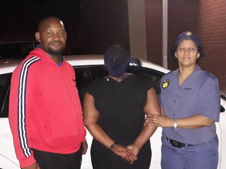 Police with an alleged fraudster who was caught red-handed in Kimberley on Wednesday.