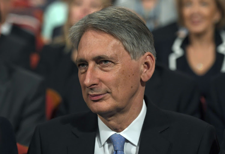 Britain's Chancellor of the Exchequer Philip Hammond listens as Prime Minister Theresa May gives a speech. Picture: REUTERS
