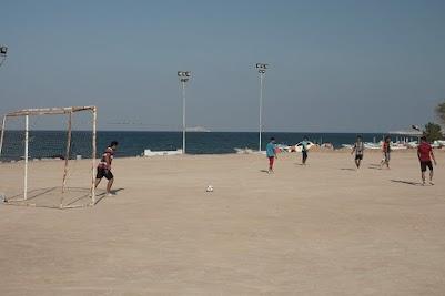 Jungs speilen Fußball am Strand von Maskat