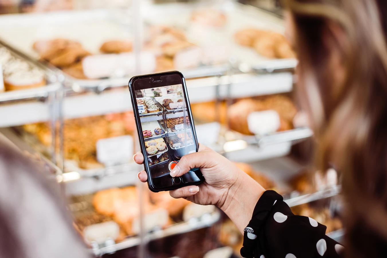 Uma usuária da Realidade Aumentada mira seu celular para um demonstrativo de produtos dentro de uma padaria.