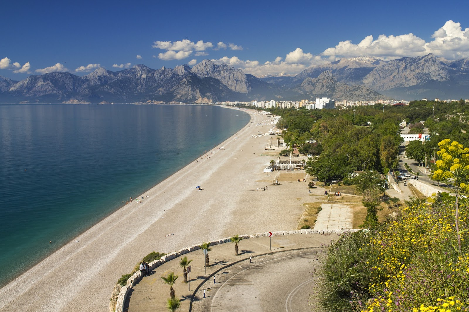 antalya long wide beach calm blue sea mountains in background and curved road in foreground sunny day in turkish riviera