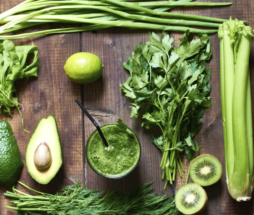 Fresh green smoothie surrounded with ingredients