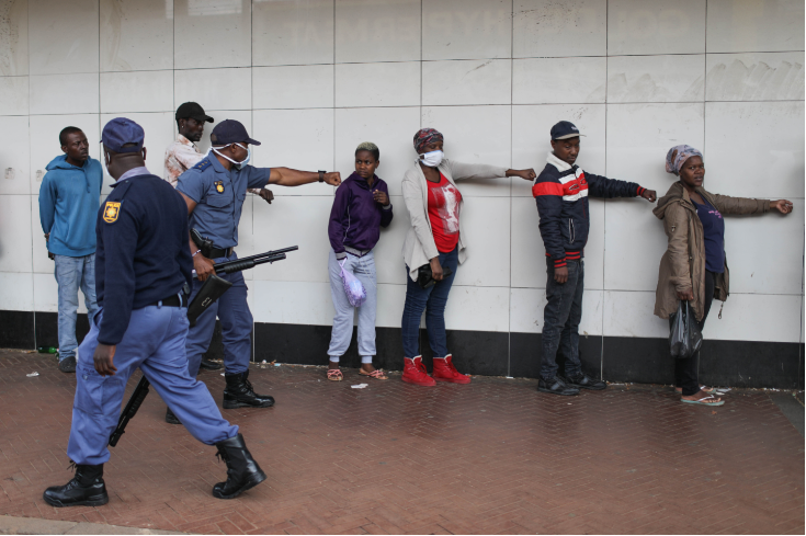 A policeman shows people how to social distance in Hillbrow, Johannesburg.