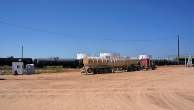 Photo: A tank truck with a unit train of railroad tank cars behind.