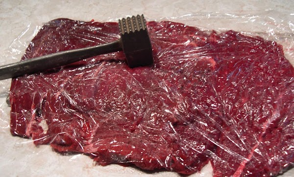 Place butterflied beef on saran wrap top and bottom. Use a meat tenderizer or...