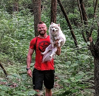 A photo of Rusty, who is a strong young man wearing a red t-shirt, holding his fluffy white dog in one arm.