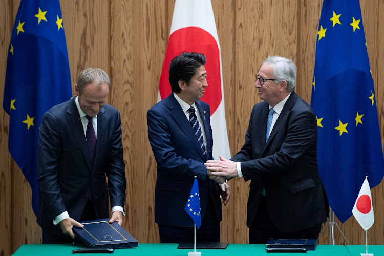 Japan's Prime Minister Shinzo Abe shakes hands with European Commission President Jean-Claude Juncker and European Council President Donald Tusk after signing a contract at the Japanese prime minister's office in Tokyo, Japan, on July 17 2018. Picture: REUTERS/MARTIN BUREAU