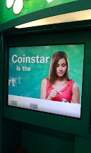 Photo: The Coinstar in Brookshire's store #30 is just inside the door, near the checkouts. The bright screen is always flashing a new message that is very eye-catching. The front panel has a picture of several coins falling and The Boy loves them!! This is the startup screen for the Coinstar kiosk.