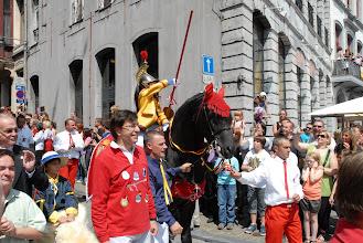 Photo: Tandis que le jeune Saint Georges fait des moulinets, l'adulte qui a tenu ce rôle le dimanche précédent tient la bride du cheval., avec à ses côtés le bourgmestre, vêtu de rouge .