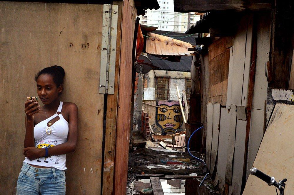 Menina ao celular na favela