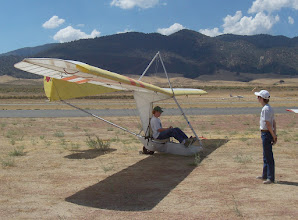 Photo: A prospective pilot sits in Goat4, hoping for more wind. The wheel is chocked so the glider will not roll backwards while windjamming, which means just operating the controls on the ground for practice. This is harder to do well than actual flying. This was at Tehachapi, California, September 1, 2007.