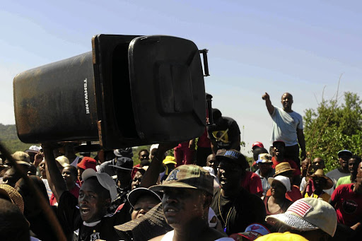 Protesting residents in Ga-Rankuwa, north of Pretoria, throw a dustbin into the City of Tshwane premises.